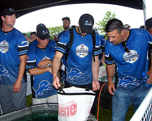 Mark Zona checks out eventual winner Don Watts (2nd from left) big Kent Lake bass during the June 10th 2013 KVD Charity Classic charity bass fishing tournament