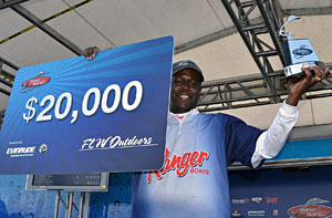 Co-angler champion Aymon Wilcox shows off his trophy and $20,000 check