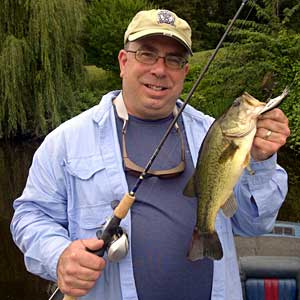 Mark cameraguy Gomez with his biggest largemouth bass of the day from the Grand River in Lansing