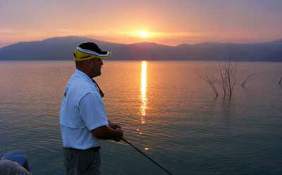 Sun sets on an angler fishing thorn trees on giant bass Mexican bass lake Comedero.