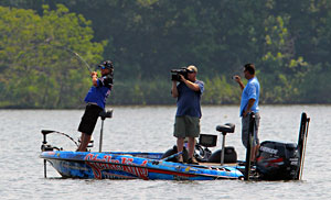 Legendary bass pro Denny Brauer maintains a strong lead on day three of the 2011 Elite Series Diamond Drive on the Arkansas River hooking a bass in front of Mark Zona and cameraman James Massey