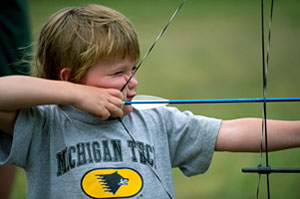 Photo of a young boy shooting a bow and arrow. Archery is one of the many DNR-sponsored activities families can enjoy during Detroit River Days.