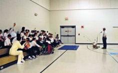 Dan Kimmel speaking to students in their gymnasium